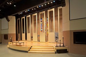 At Concord United Methodist Church in Knoxville, TN, acoustical partitions hide band equipment in a multi-use worship room. Custom cut-outs ensure the space's stained glass windows are always visible.