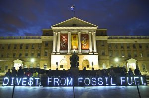 Activists support fossil fuel divestment in front of the University of Wisconsin-Madison's Bascom Hall on April 5, 2014. Fossil fuel divestment has gained support from a growing number of religious organizations, including Union Theological Seminary, World Council of Churches, the Unitarian Universalists and the United Church of Christ. Creative Commons image by Light Brigading