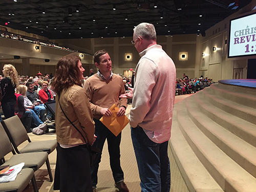 Pastor Lance Taylor convenes with church members after a recent worship service.