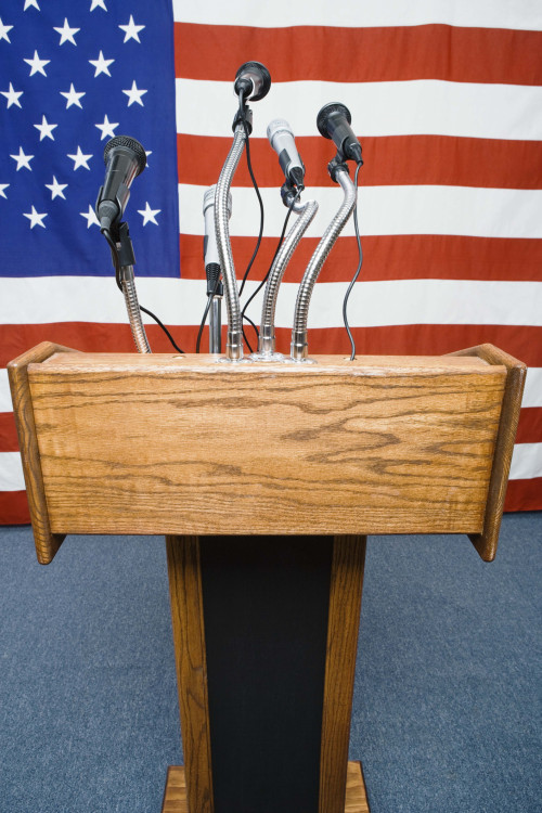 Podium with microphones by American flag
