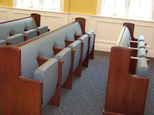 Combination upholstered pew back with flip-up auditorium seat