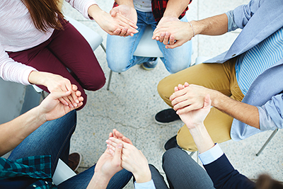 Group of students holding by hands while sitting in circle