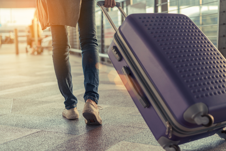Traveler with suitcase in airport concept.Young girl walking with carrying luggage and passenger for tour travel booking ticket flight at international vacation time in holiday rest and relaxation.